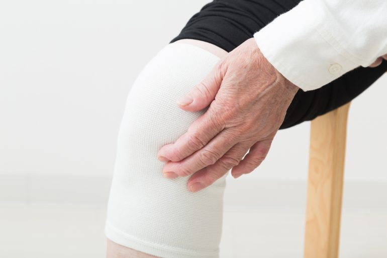 膝をおさえている男性